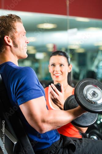 Trainer und Mann mit Hanteln im Fitnessstudio