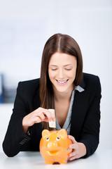 frau steckt geldschein in ein sparschwein