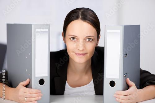 lächelnde frau mit zwei aktenordnern
