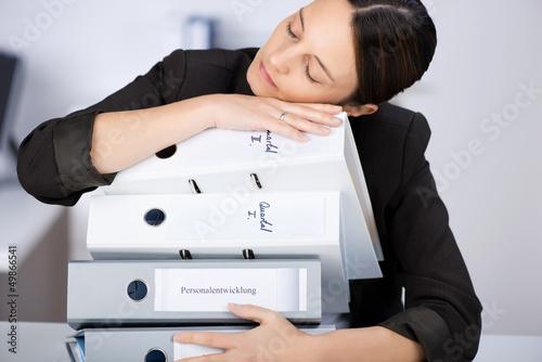 frau schläft auf einem stapel aktenordner