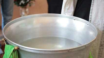 priest blesses baptismal font