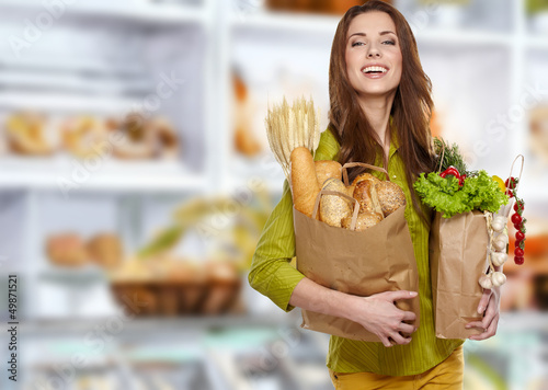Woman in market  holding a grocery bag full of bread