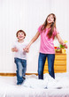 Laughing siblings jumping