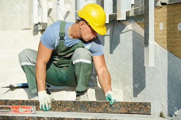 tiler at granite stairs way construction works