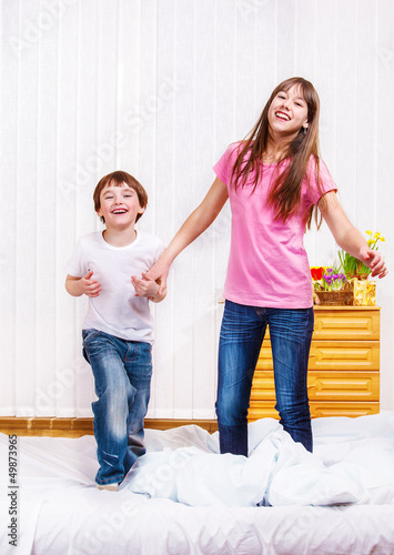 Laughing siblings jumping
