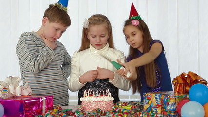 children blowing candles on birthday cake