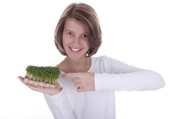 Glückliches Mädchen zeigt auf Gartenkresse