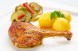 Roast duck leg with potatoes and pickes on the plate