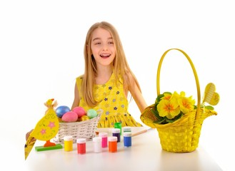 Smiling little girl painting Easter eggs.