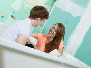 Young couple sit in the bathtub of their site and have fun