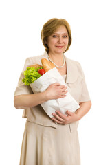 An elderly woman holds a package with vegetables in the hands