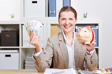Frau im Büro mit Geld und Sparschwein