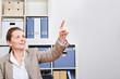 Frau im Büro hält Zeigefinger hoch