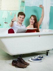Young couple celebrate the bathtub in a building lot