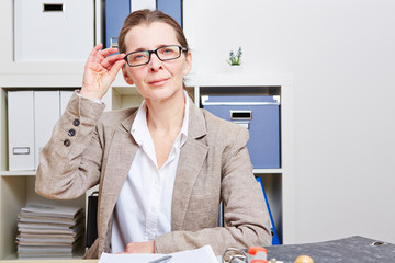 Frau im Büro schaut durch ihre Brille