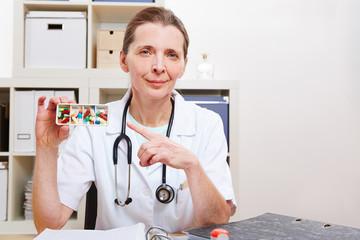 Ärztin zeigt auf Medikamente in der Klinik