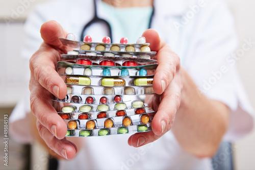 Hände halten viele bunte Tabletten