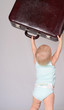 baby girl playing with suitcase on grey background
