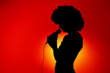 Silhouette of singing woman with microphone
