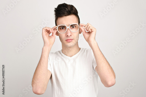 Confused, disturbed, upset.Young man with glasses frowning.