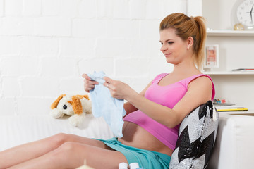 Pregnant  woman with children's clothes.