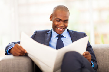 handsome african corporate worker reading newspaper in office