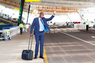 african american businessman calling taxi in airport
