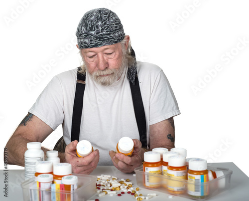 Senior holding prescription bottles with pills on table