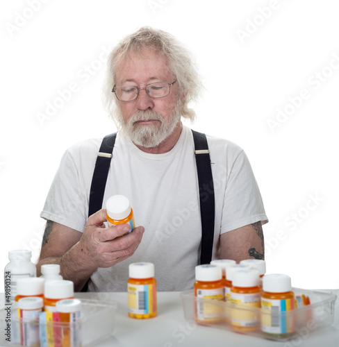 Senior looking at a bottle of pills