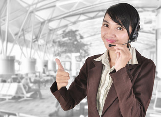 Call center woman with headset showing hand ok, in the office