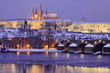 Night colorful snowy Prague gothic Castle with Charles Bridge