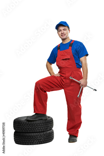 automobile mechanic with car tire and spanner