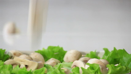 Sliced ​​mushrooms are falling on the leaves of lettuce.