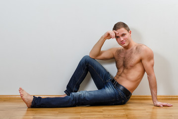 Handsome guy in jeans with bare torso sitting on the floor