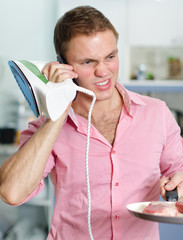 Young man with pan and iron speaking on the phone
