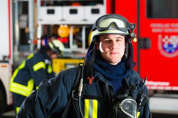 Feuerwehrmann steht in Uniform vor einer Feuerwehr