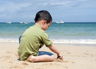 Child sitting on a beach, playing with a sand.