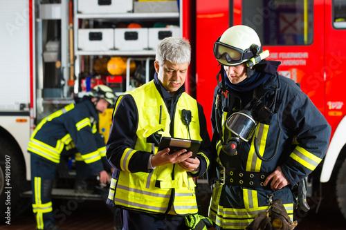 Leinwandbild Motiv Feuerwehr - Einsatzplanung am Tablet-Computer