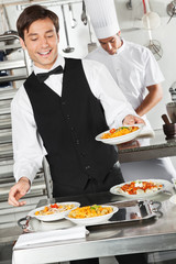 Waiter Holding Pasta Dish