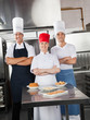 Confident Chefs With Sweet Dishes On Kitchen Counter