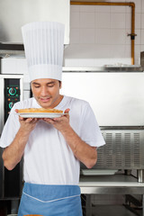 Chef Smelling Sweet Dish In Kitchen