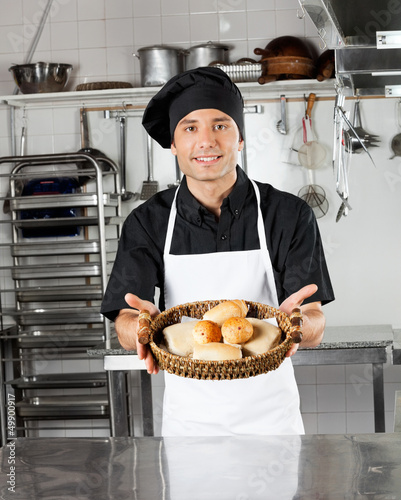 Young Chef Holding Basket Of Breads