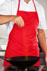 Chef Adding Turmeric Powder In Pan