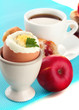 Light breakfast with boiled egg and cup of coffee, close up