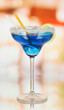 Blue cocktail in glass on room background