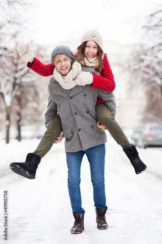 Man giving woman piggyback in winter setting