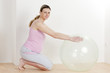 pregnant woman doing exercises with a ball