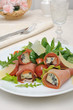 Rolls of jamon with blue cheese in the mix of lettuce with Parme