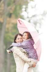 Mother and daughter under umbrella in autumn.