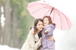 Happy mother and daughter in park in rain.